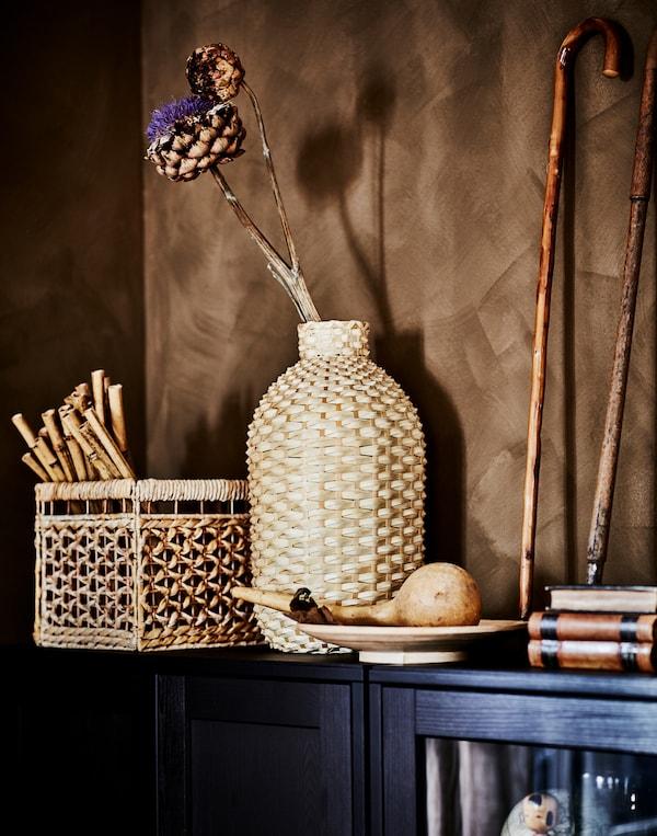 KAFFEBÖNA dekorativna vaza od bambusa i dekorativni detalji od organskih materijala na vrhu tamnog, braon HAVSTA ormarića.