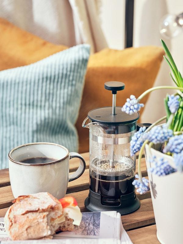 Kaffepress på balkongbord i vårsolen.