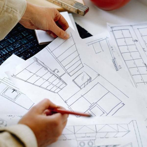 Kaksi kättä pitää papereita ja kynää. Paperilla kuvia suunnitelmista.