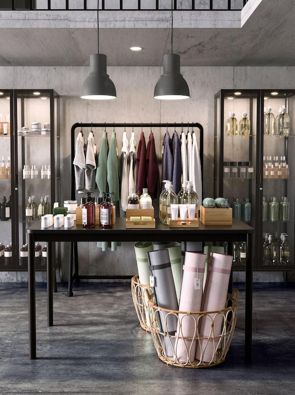 Kaksi MILSBO-vitriinikaappia ja TURBO-vaateteline pitävät myymälän tuotteet kauniisti esillä. Lattialla SNIDAD-kori.