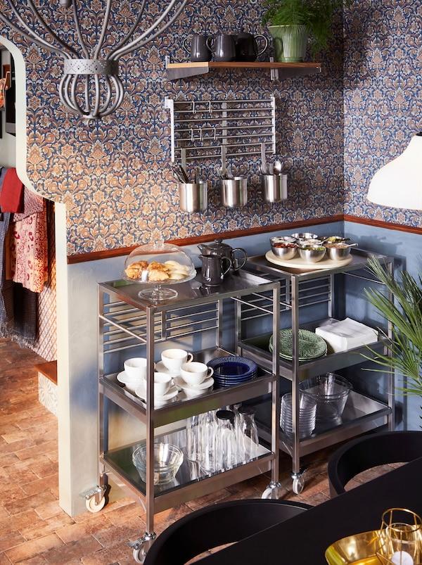 Kaksi ruostumattomasta teräksestä valmistettua KUNGSFORS-tarjoiluvaunua. Tarjoiluvaunuissa ruuat ja astiat kauniisti esillä. Ruokailuvälineet on kätevästi aseteltu kulhoihin, jotka roikkuvat seinälle kiinnitetystä telineestä.