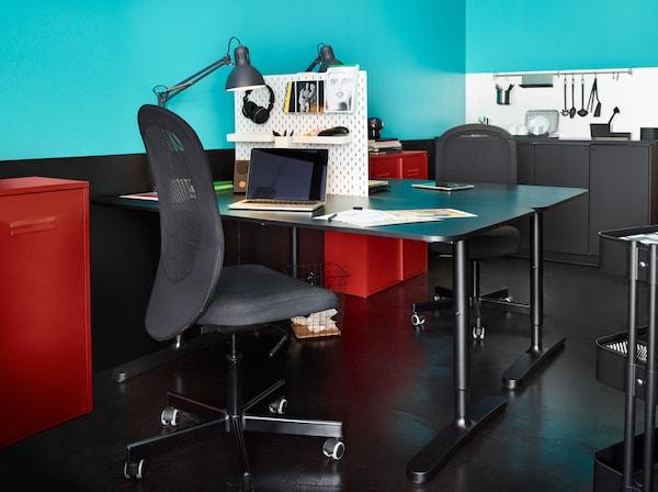 Kaksi vastakkain olevaa työpöytää, joiden välissä SKÅDIS-säilytystaulu antamassa yksityisyyttä. Molemmissa työpisteissä musta FLINTAN-toimistotuoli, TERTIAL-työvalsisin ja punainen IVAR-kaappi.