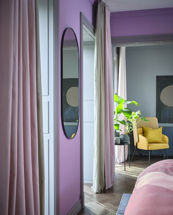 KALKFLY light pink curtains and KALKFLY dark beige room darkening curtains hang by large windows and cover half of them.