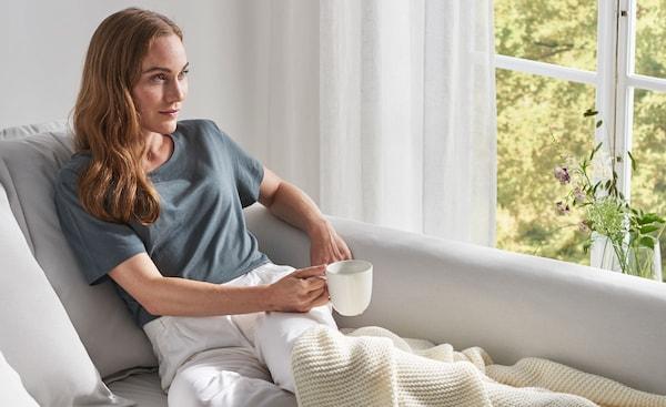 Kanapén pihenő nő, egy csésze teával és takaróval.