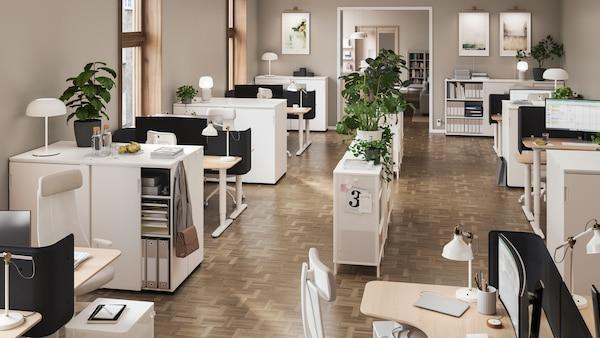 Kancelária s otvorenými a zatvorenými úložnými priestormi, policami na predelenie miestnosti, pracovnými stolmi, sedením, rastlinami a zavesenými plagátmi.