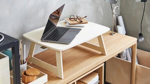 Kannettava tietokone, muistivihkoja ja silmälasit koivuvanerisen RÅVAROR-tarjottimen päällä joka on tammiviilutetun RÅVAROR-sivupöydän päällä.