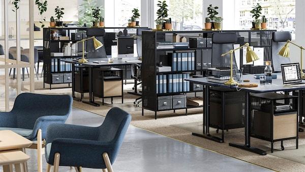 Kantoorruimte met zit-/stabureaus, stellingkasten, stoelen en slimme opbergers.
