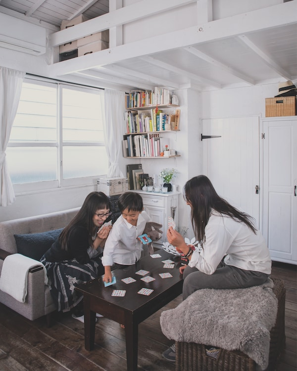 Kaoli, Shige and Tokiwa play card games at their black coffee table in the living room space of their small white home.