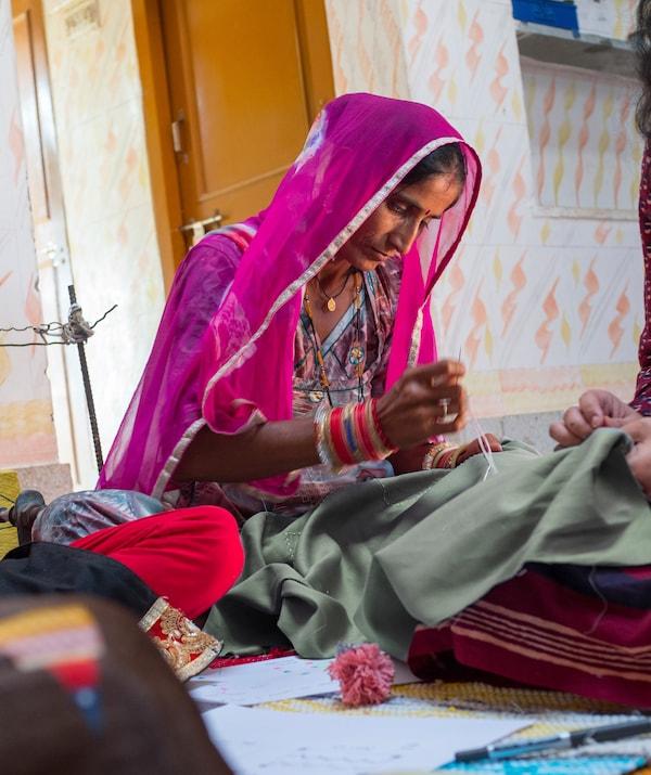 カラフルな民族衣装と透けて見える生地のショールを身に着け、ほかの女性と一緒にラグの上に座って針仕事をしている女性。
