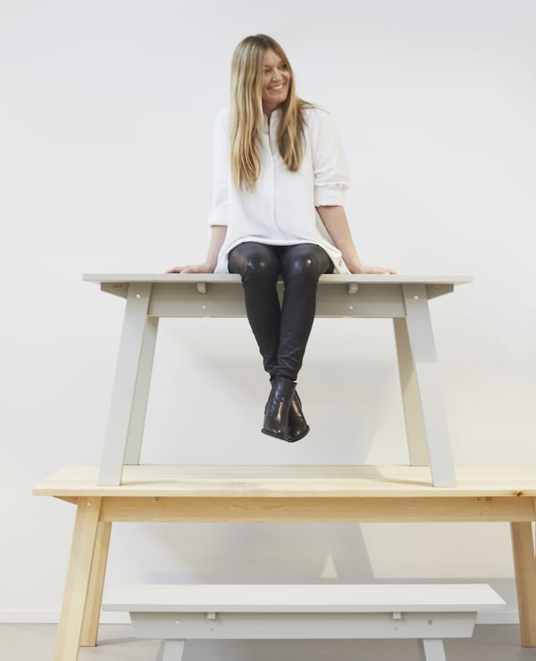 Karin Gustavsson sitting on a stack of benches.