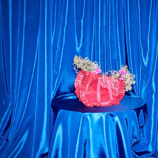 KARISMATISK kasse i rosa med volanger ståendes på blått draperat silkigt tyg.