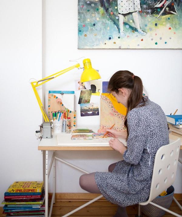 Karlotta zeichnet an ihrem Schreibtisch, sie sitzt auf JULES Schreibtischstuhl für Kinder in Weiss.