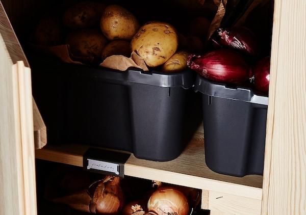 Kartoffeln und Zwiebeln in schwarzen Kunststoffbehältern in einem Schrank