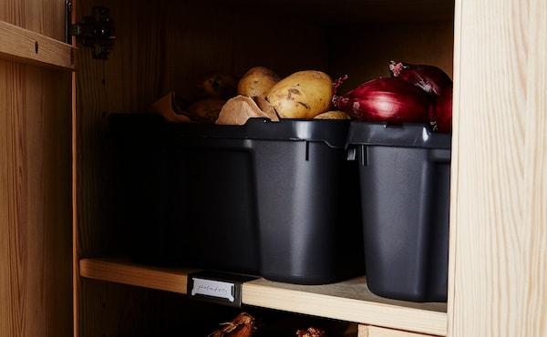 Kartoffeln und Zwiebeln in Vorrats-Boxen im Schrank verstaut