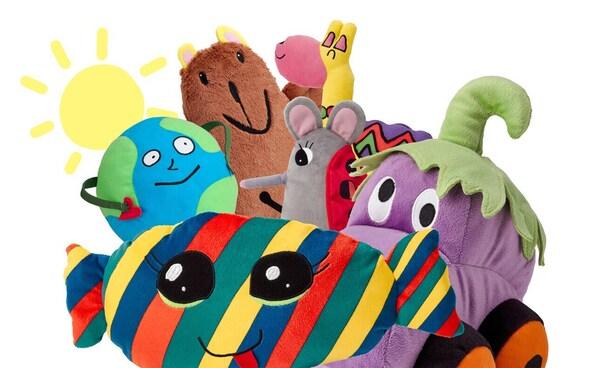 Картонный замок коричневого цвета в качестве фона. Впереди шесть разноцветных мягких игрушек ИКЕА из коллекции САГОСКАТТ, созданной по мотивам детских рисунков.