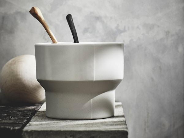 Кашпо ХАНТВЕРК ручной работы стоит на скамье. По центру виден стык литейной формы.