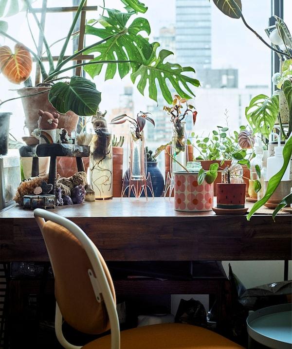 Kaspók és vázák egy fa íróasztalon, narancssárga forgószékkel.