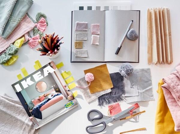 Katalog IKEA 2021, zvezek za ideje, škarje ter kosi blaga v bledih pastelnih barvah in toplih gorčičnih odtenkih.