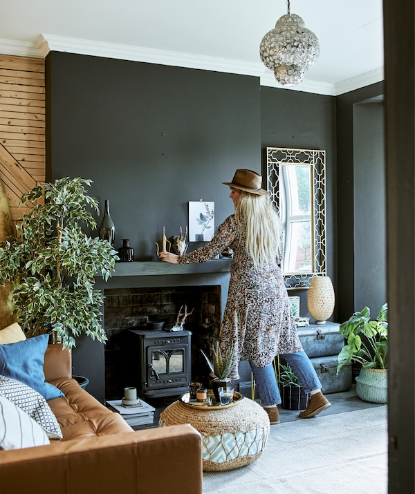 Katty järjestää koristeita takan yläpuolella olohuoneessa, jossa tummat seinät ja ruskea nahkasohva.