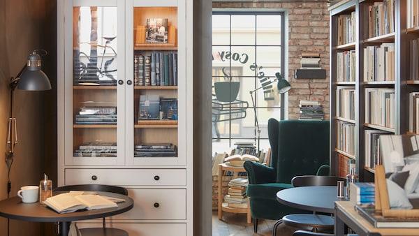Kaviareň s kaviarenským nábytkom a veľkými knižnicami s knihami, bodovými lampami a kreslom s tmavozelným zamatovým poťahom.
