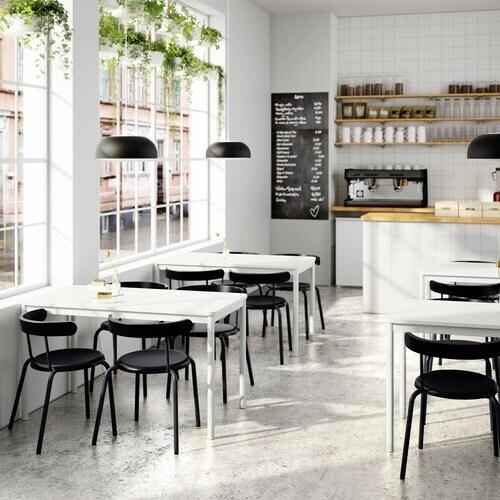 Kawiarnia z jasnymi stolikami i czarnymi krzesłami