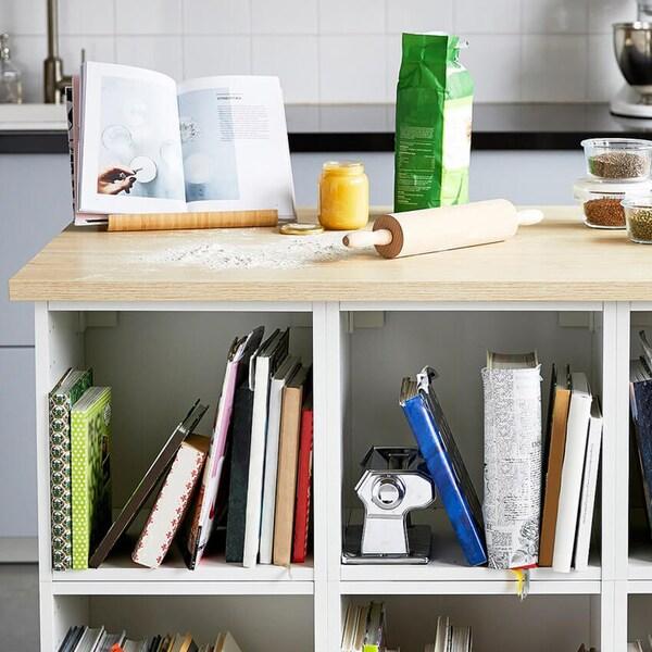 Keittiö, jonka etualalla valkoinen keittiösaareke jossa puinen työtaso. Tasolla leivontatarvikkeita, lasipurkkeja ja musta, kivinen mortteli.