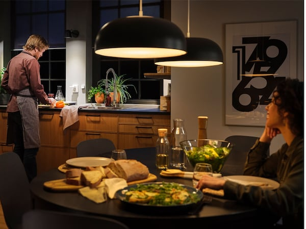 Keittiö, jossa on suuri lämpimästi valaiseva kattolamppu. Nainen istuu pöydän ääressä ja mies kokkaa keittiössä kirkkaassa valossa.