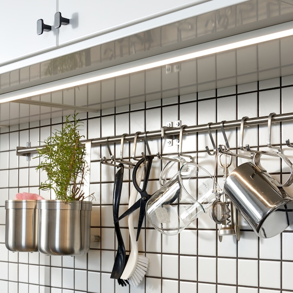 Keittiö, jossa valkoiset kaappiovet, ja niiden alla on valkoinen laattaseinä, jossa on asennettu kisko ja koukut ruostumattomasta teräksestä.