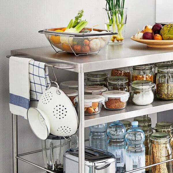 Keittiökaappien vieressä on teräksinen tarjoiluvaunu, jonka hyllyillä purkeissa erilaisia ruoka-aineita.