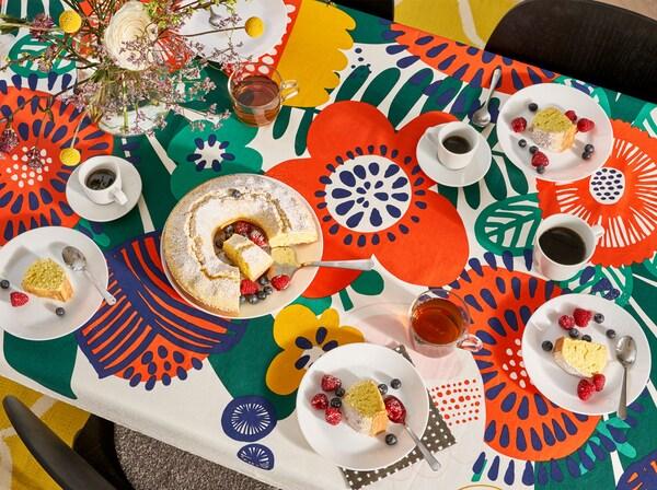 Keittiön pöytä, jolla on kukkakuvioinen pöytäliina, lautaset, lasit, mukit ja kakku.
