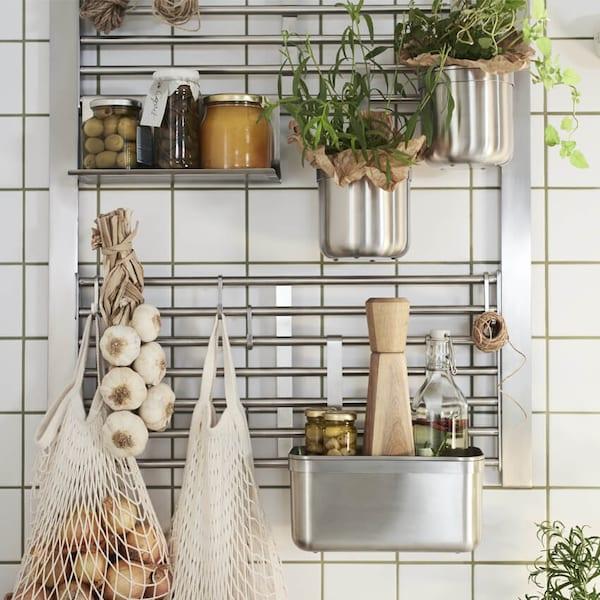 Keittiön seinä, jossa KUNGSFORS-seinäverkko, hylly, koukut ja astiat, kaikki ruostumatonta terästä.