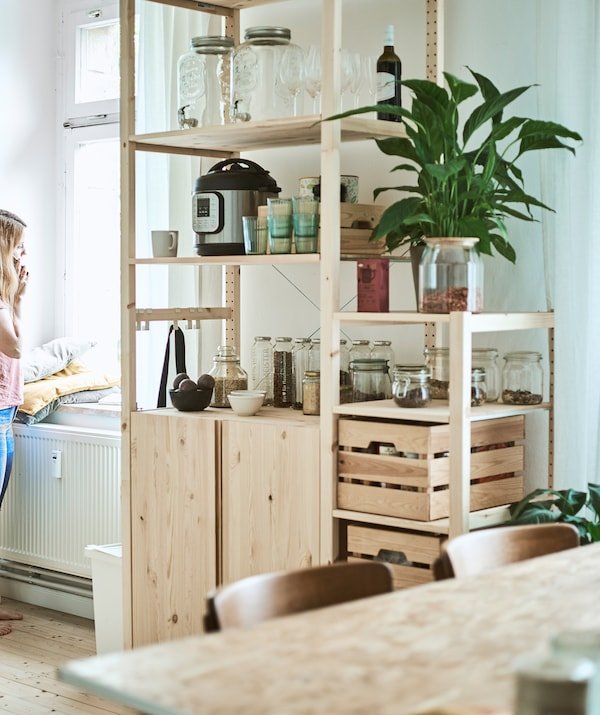 Keittiössä korkea, puinen hylly, jossa on lasipurkkeja, puisia laatikoita ja keittiölaitteita.