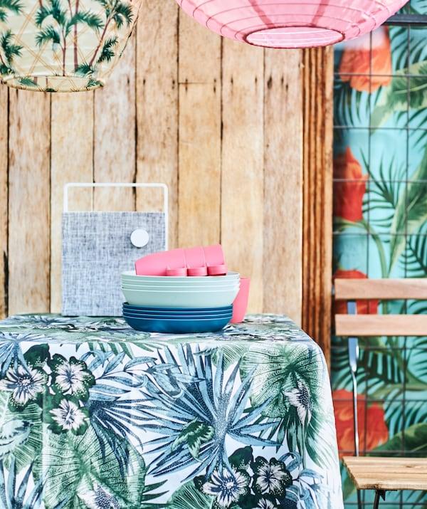 Kék és zöld levélmintás méteráru egy asztalon, kék tányérok, fehér hangfal és lámpások.