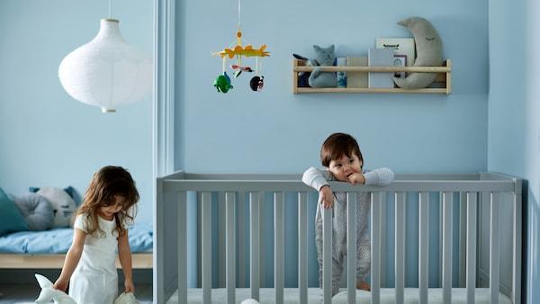 Kék gyerekszobában kisfiú áll egy rácsos ágyban, mellette a nővére a szobában.