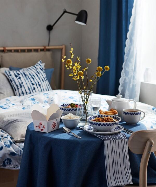 Keleti stílusú egyszemélyes vacsora, többfogásos étel egy kis kerek asztalon egy ágy mellett.