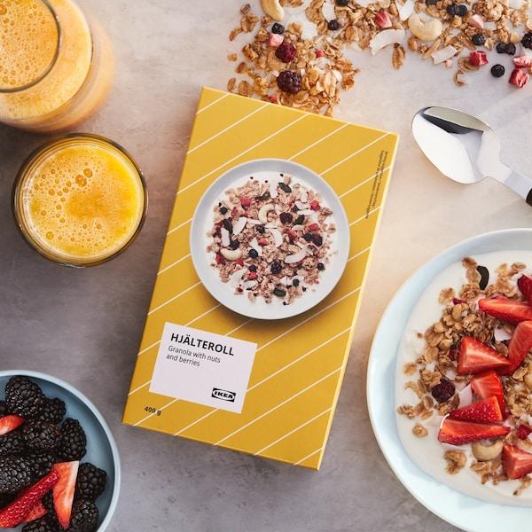 Keltainen HJÄLTEROLL granola -paketti pöydällä, jossa tuoremehua lasissa ja jogurttiannos.