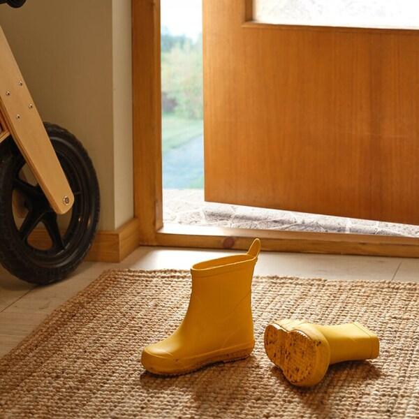 Keltaiset lasten saappaat LOHALS-matolla käytävällä, osittain avoimen ulko-oven vieressä.