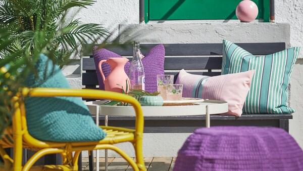 Kényelmes kis sarok az erkélyen természetes anyagokból készült székekkel, lábtartóval és színes párnákkal.