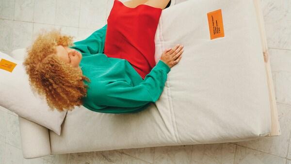 Kényelmesen pihenő nő egy fa heverőn, szürke matraccal.