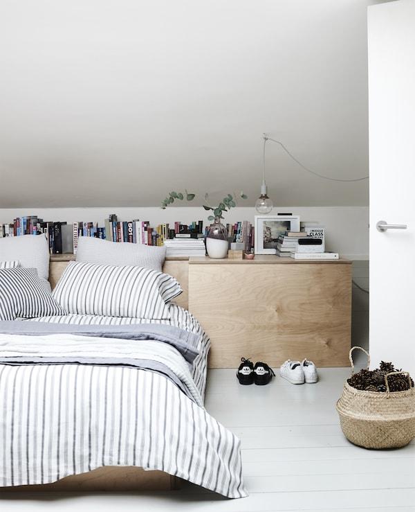 Kerrostettuja tekstiilejä minimalistisessa makuuhuoneessa.