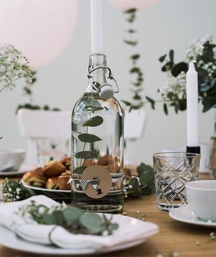 Kerzenständer aus einer Glasflasche auf einem weiß-grün gedeckten Tisch