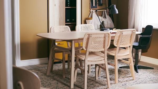 Keskellä oliivinväristä huonetta neljän hengen ruokailupöytä, jossa kauniit rottinkituolit.  Ruokapöydän alla vaalea matto.