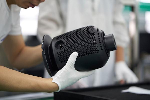 Két fehér kesztyűs kéz tartja a fekete SYMFONISK asztali lámpa WiFi-s hangfal talpát a gyárban.