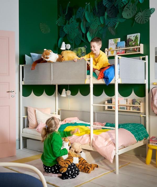 Két gyermek egy zöld és fehér gyerekszobában, emeletes ágyakkal és falipolcokkal.