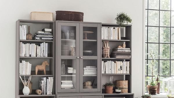 Két IKEA HAVSTA polc, nyitott tárolókkal és üvegajtókkal, tömör fenyőből.