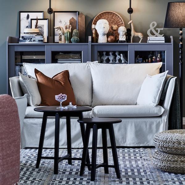 Két kerek asztal egy világos, kétszemélyes kanapé előtt, mintás szőnyegen. Mögötte egy üvegajtós könyvespolc áll.