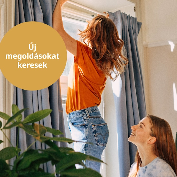 Két lány BOTAREN zuhanyfüggönyrúdra akasztott függönyt szerel az ablak fölé.