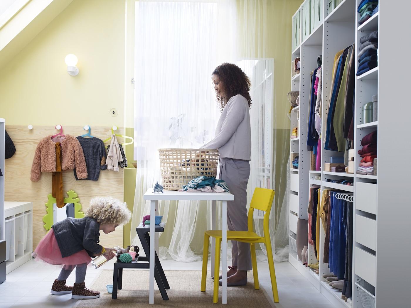 Két lány rendet rak a szobájában.