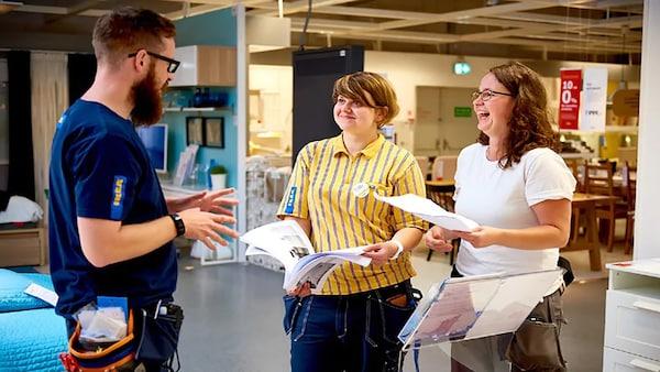 Két nő és egy férfi, IKEA egyenruhában beszélgetnek.