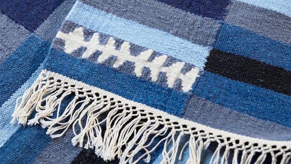 Kézzel készült csíkos TRANGET gyapjúszőnyeg, fehér, fekete és szürke színben és különböző kék árnyalatokban.